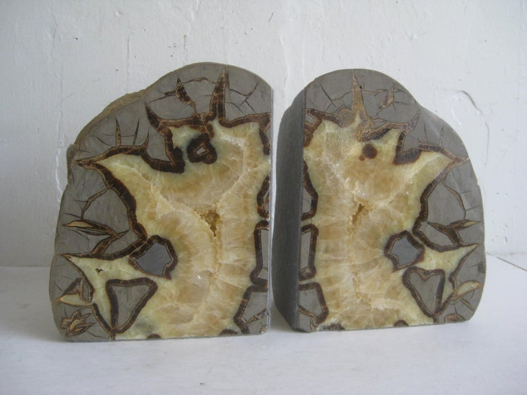 Beautiful pair of vintage natural geode bookends. This was a large stone that was split to make the bookends. Matching pair with a polished face. Has felt protective material on the two sides. Natural rock on the back. One has a little nick on the
