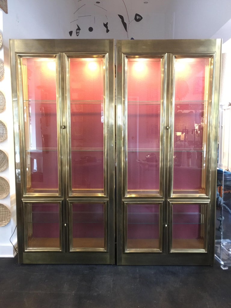 Pair of brass mastercraft cabinets / vitrines with bevelled glass doors and four interior adjustable shelves. Wonderful brass molding throughout - two downlights in each cabinet.  American, circa 1970s. Having four doors/ four glass shelves and