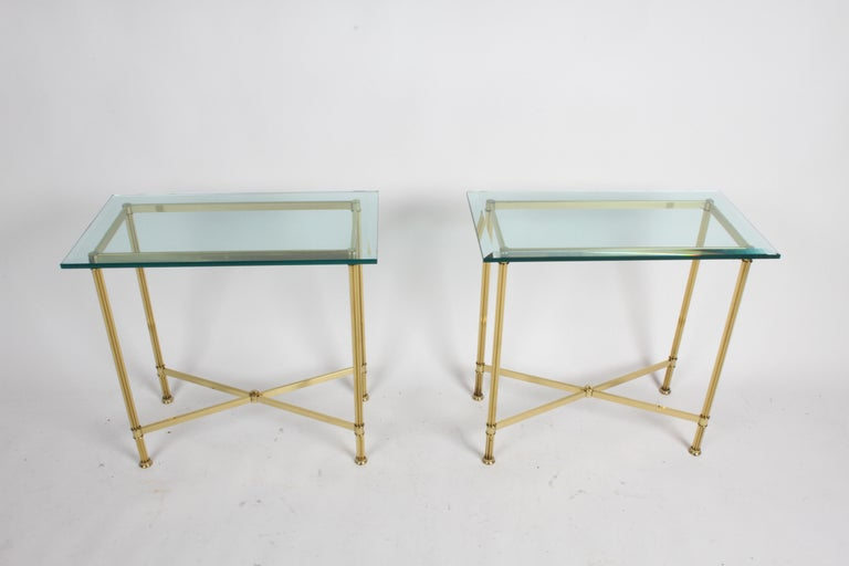 Pair of matching Mastercraft rectangle console tables with beveled glass tops on elegant fluted brass column legs with X-stretcher bracing. Brass is in very nice condition, with factory applied patina. Few minor chips to corners of glass, glass is