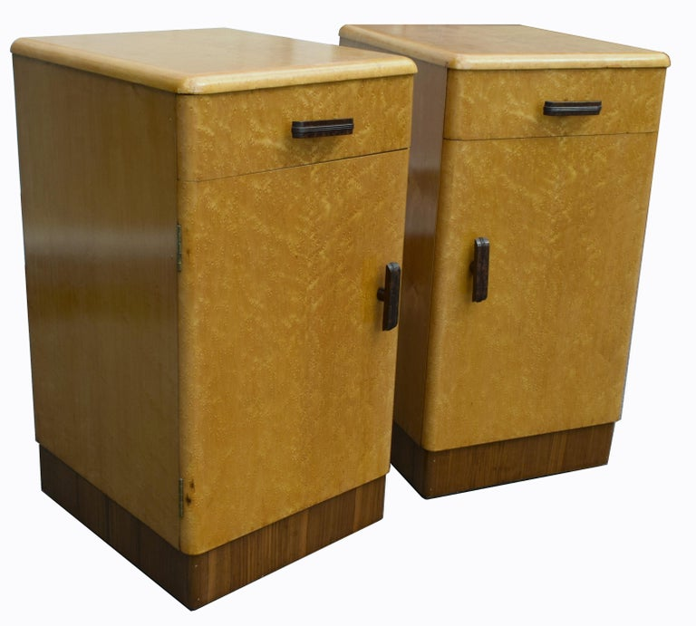 Fabulous pair of matching 1930s Art Deco bedside cabinet tables in a lovely blonde bird's-eye maple and walnut veneer. These cabinets originate from England and feature a pull out / pull-out drawer to the top which retains its original Bakelite