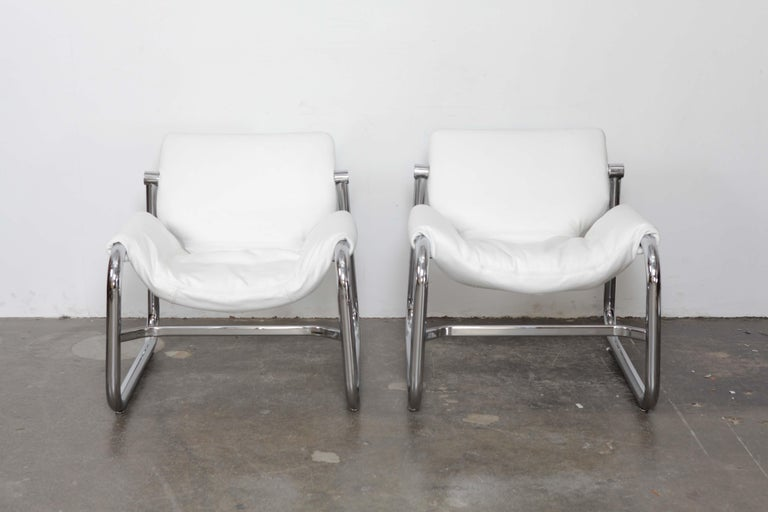 Pair of white leather and chrome tubular metal framed lounge chairs designed by Maurice Burke for Pozza, Brazil, 1960s. Newly upholstered in Italian white leather.