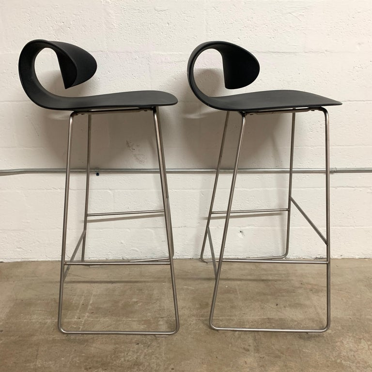 Sculptural pair of barstools rendered in molded polycarbonate with a steel frame and footrest designed and manufactured by Sawaya & Moroni.