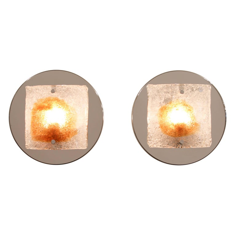 A lovely pair of Mazzega sconces featuring clear, handblown glass with amber inclusions in the center of each piece, Italy, circa 1970s. Crushed glass is fused to the back of each piece, producing a lovely texture and a rich, warm glow when lit.