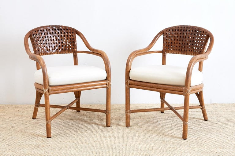 Organic modern pair of genuine McGuire bamboo rattan armchairs featuring a woven leather seat back. Graceful frames constructed from bent rattan with curved arms and seat. Linen upholstered seat cushion and reinforced with leather rawhide strapping.