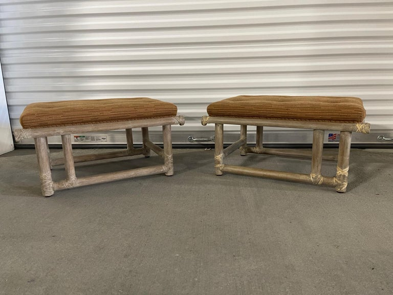 Pair of mid-century lacquered bamboo ottomans or foot stools featuring a Cerused or whitewashed finish with woven leather straps and stretchers. Signed McGuire on a brass label.