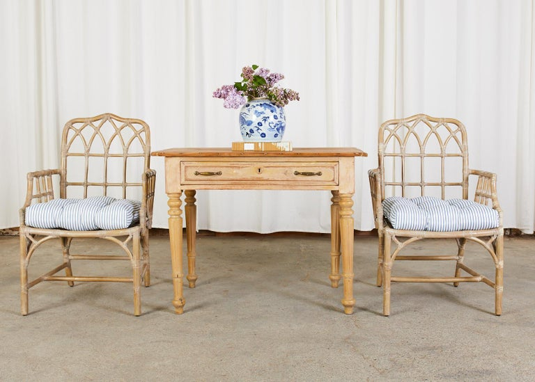 Distinctive genuine pair of McGuire bamboo rattan dining armchairs featuring a cerused lacquer finish. The chairs are crafted from rattan poles with a gothic lancet arch design on the backs and an open fretwork on the sides in a Chinese Chippendale