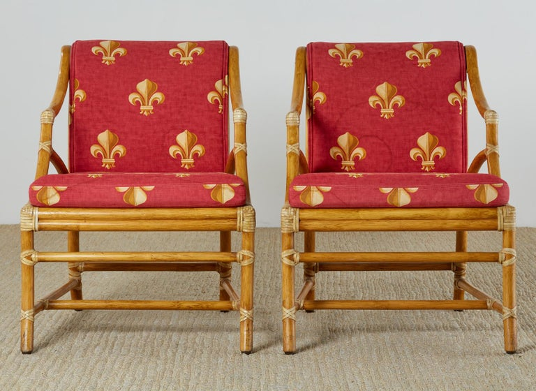 Stylish pair of genuine McGuire lounge chairs or club chairs featuring a caned seat and back designed by Elinor McGuire with gracefully curved, and bent rattan reinforced with light colored leather rawhide laces. Topped with crimson colored fabric