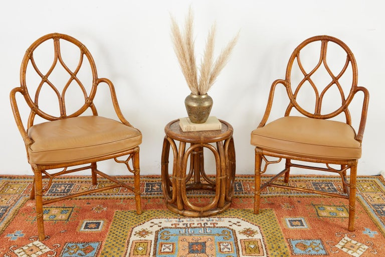Handsome pair of bamboo rattan dining chairs made in the California organic modern style by McGuire San Francisco. The chairs have a round back with gracefully curved arms conjoined to a cane seat topped with a thick leather seat cushion. The chairs