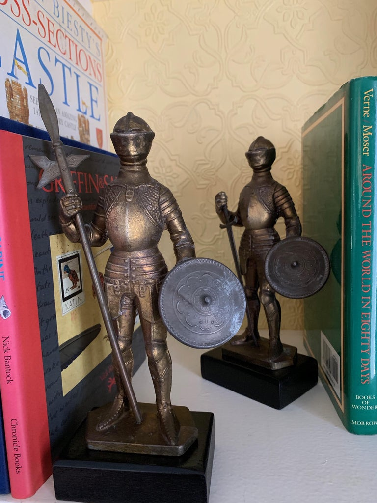 A fantastic pair of lit metal knights with removable swords, that could be used for letter openers... each knight is holding a shield and stand atop a black wood base. The pair are of substantial weight, at 1.5 pounds each.... and handsome on any