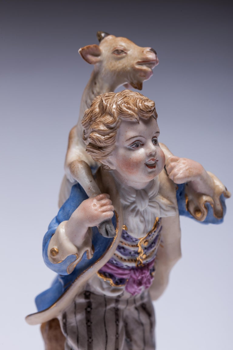 Beautiful hand-painted porcelain figures of a boy carrying a goat.