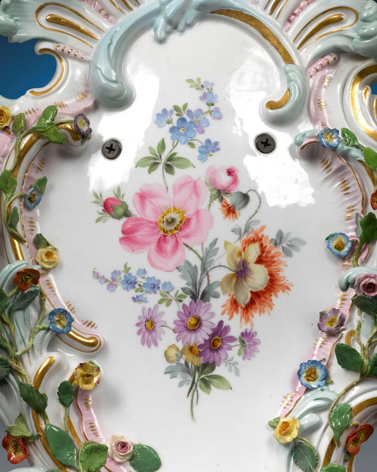 This remarkable pair of Meissen Porcelain wall sconces is crafted with all of the exquisite detail and splendor of the Rococo period. Exquisitely hand painted with gilt accents, each fixture is adorned with elaborate, classic Rococo decoration,