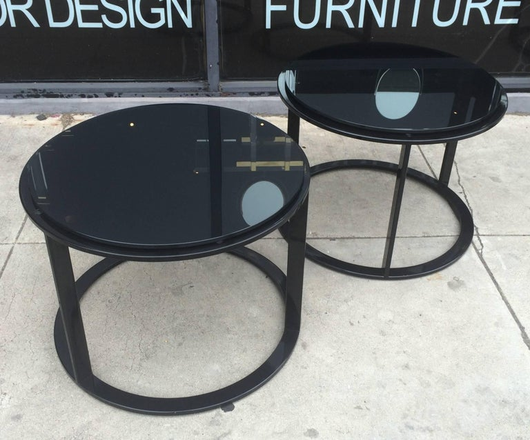 Beautiful set of side tables in black tubular steel and reverse painted black glass tops designed by Antonio Citterio and manufactured by B&B Italia.  These tables can be used together or separate and they are perfect for small places or