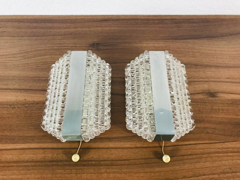 A pair of midcentury wall lamps by Kaiser made in Germany in the 1960s. It is fascinating with its Space Age design and unique glass shades. The body of the light is made of full metal.