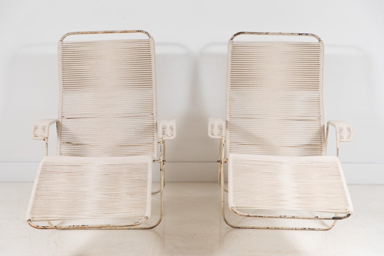 Pair of metal and rope outdoor lounge chairs in the style of Walter Lamb. The metal frame offers a rustic aged patina, the natural white rope has been newly woven to the frames. The lounge chairs offer two positions for easy lounging.
