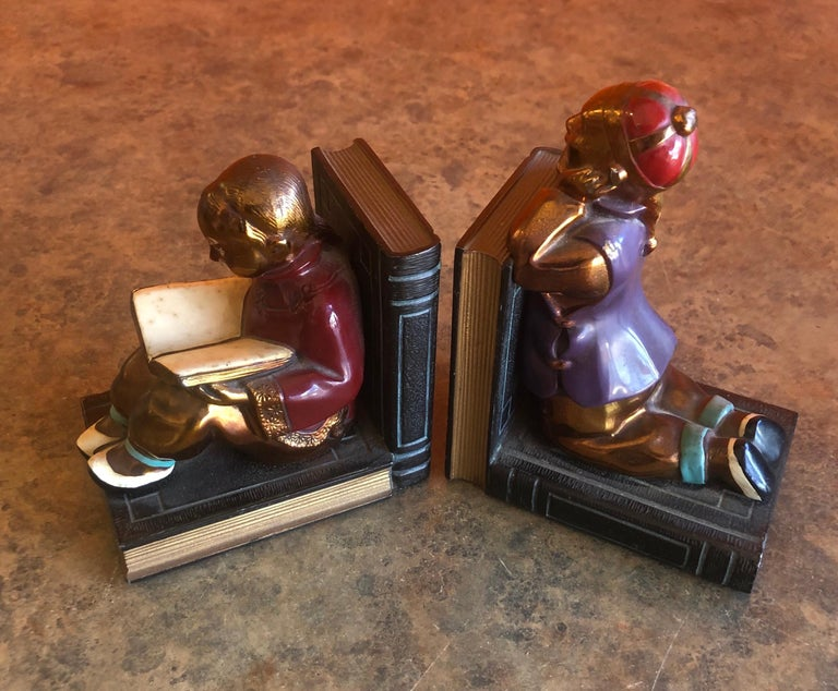Fabulous pair of metal clad Art Deco bookends by Ronson Art Metal Works, circa 1930s. The bookends depict two Chinese youngsters, beautifully sculpted; the boy is patiently observing while the girl is quietly absorbed by what she reads.  This