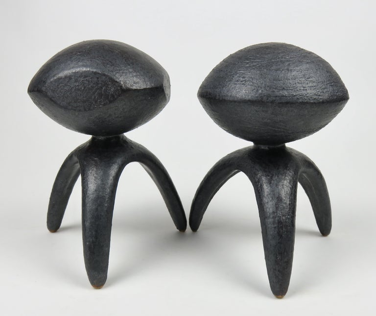 Two modern TOTEMS in a rare metallic glaze, each with a sphere on tripod legs. One sphere has carved circular lines emphasizing movement, the other sphere with flattened sides, is more structural. Both are like miniature spaceships in orbit. The