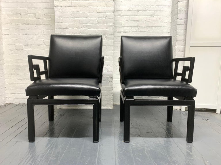 Pair of Michael Taylor for Baker Asian style chairs. The chairs have black lacquered solid wooden frames with black vinyl cushioned seats. Chairs are sturdy. Measures: 35 H x 23.25 W x 25 D. Seat height 18.5, arm height 26 H.