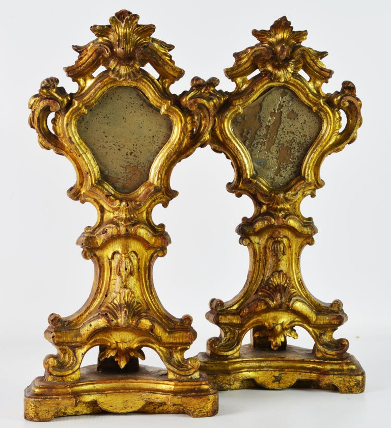 An excellent pair of richly carved Italian giltwood reliquaries now with antique glass inserts dating to the mid-19th century. The symmetrical shape and the deep and reticulated sculptural carving is typical Baroque, a style that lived on in church