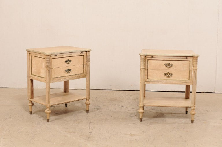 A pair of American nightstands from the mid-20th century. These vintage side chests, designed in French style, each feature rounded and fluted front side posts carved with horizontal ribbing and vertical fluting. Each front corner of the top has