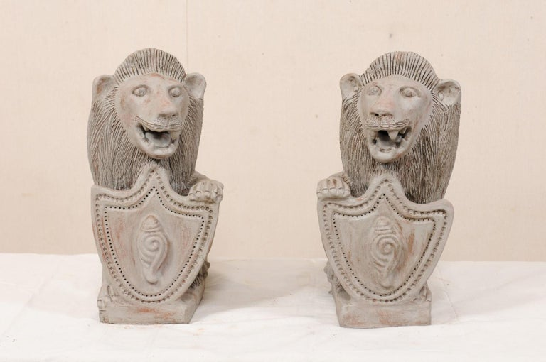 A pair of British Colonial painted terracotta lions from the mid-20th century. This vintage pair of lions from Kerala, India have each been created in a seated position with a single front leg or paw raised atop a shield, which is decorated with a
