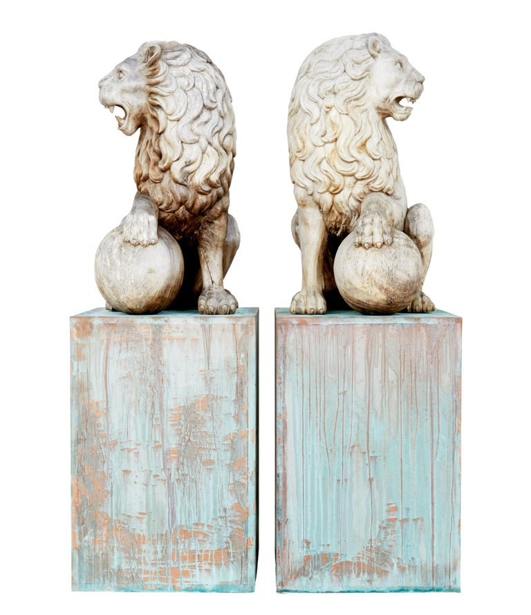 Pair of mid-20th century carved solid wood lions circa 1950.  Here we offer a fine pair of decorative carved lions for the ultimate installation piece. Heavily carved out of solid wood, seated lions with 1 paw resting on a ball. Presented on a