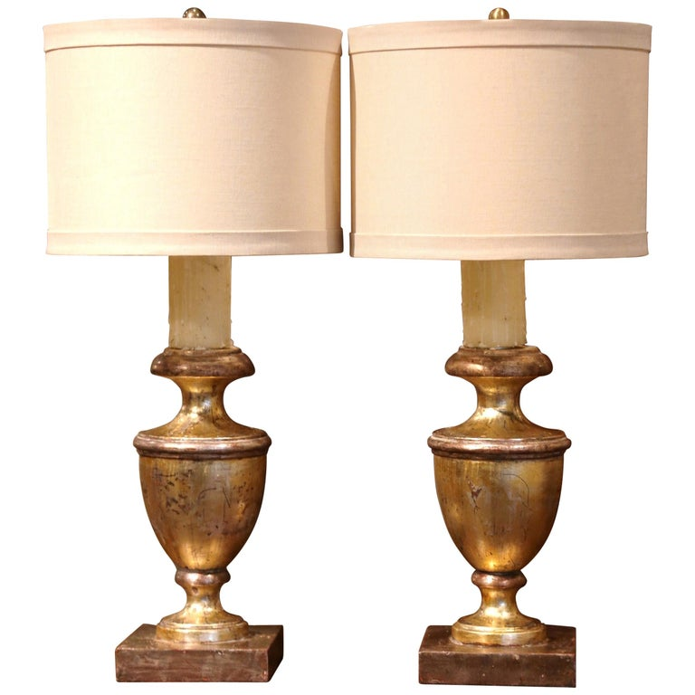 Decorate a console or a buffet with this pair of elegant table lamps! Crafted in Italy circa 1960, each hand carved urn sits on a square base and has new wiring embellished with a decorative dripping candle cover. The neoclassical light fixtures are