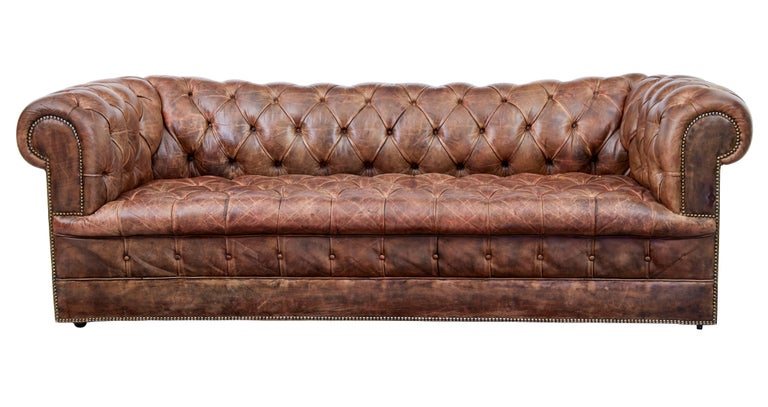 Pair of mid-20th century leather chesterfield sofas, circa 1980.  Large pair of chesterfield sofas. Beautiful quality brown leather with excellent patina. Over stuffed roll top arms and back. Each standing on castors.  2 buttons missing, some