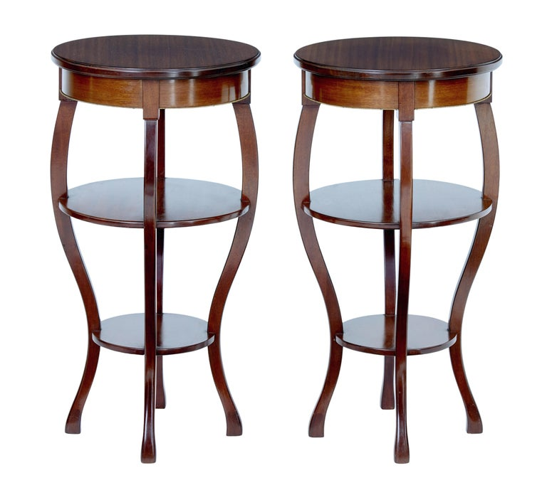 Good quality pair of occasional tables, circa 1950.  Made in mahogany and very much in the Empire taste. Circular tops with brass beading detail to the frieze. Standing on 4 sabre legs with a further 2 circular shelves supported between the