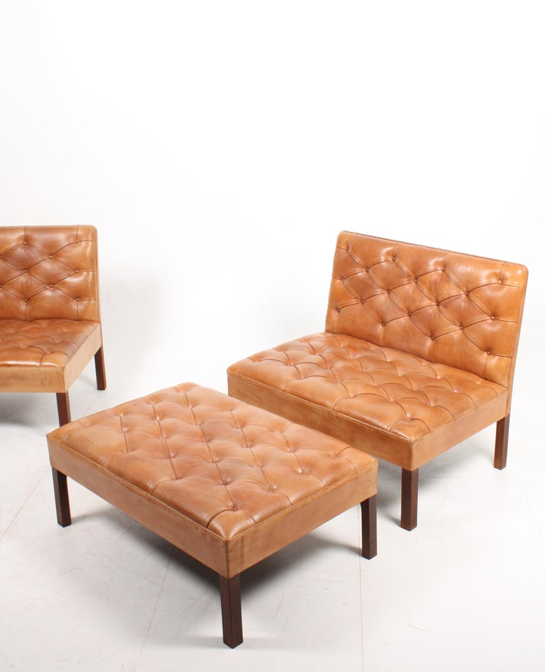Pair of addition sofas with a matching bench in patinated leather Designed by M.A.A Kaare Klint for Rud. Rasmussen in the late 1930s. Great original condition. Made in Denmark.