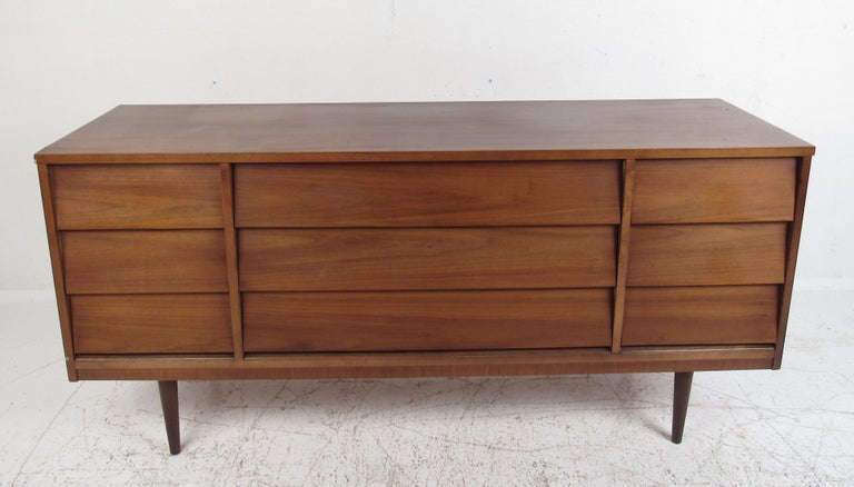 This beautiful pair of vintage modern dressers offer plenty of room for storage within their many drawers. A simple, yet stylish design with straight lines and a charming vintage walnut finish. The unusual hidden louvered drawer pulls and stubby