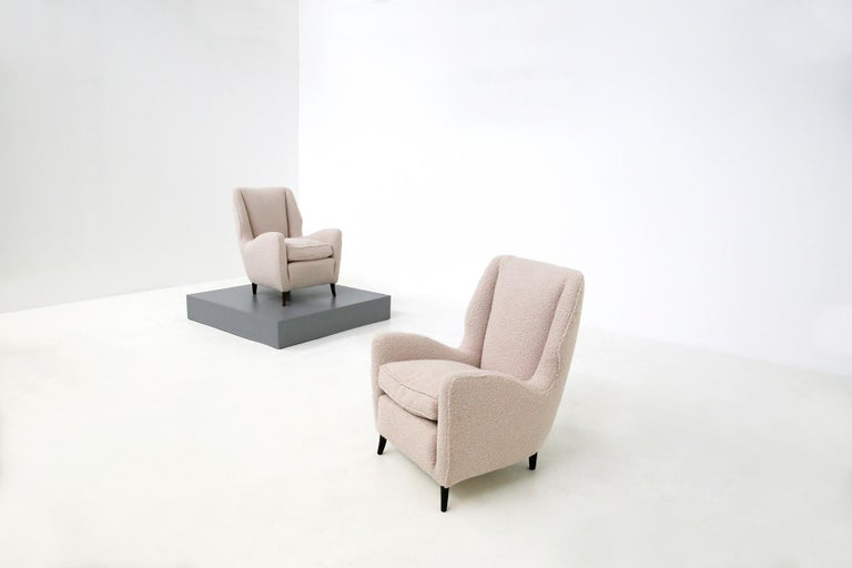 Pair of ISA Bergamo manufactured armchairs from 1950. The armchairs have been restored and reconditioned. A very fashionable white bouclè fabric has been chosen for its cover. Its conical feet are made of walnut wood. Its classic and harmonic line