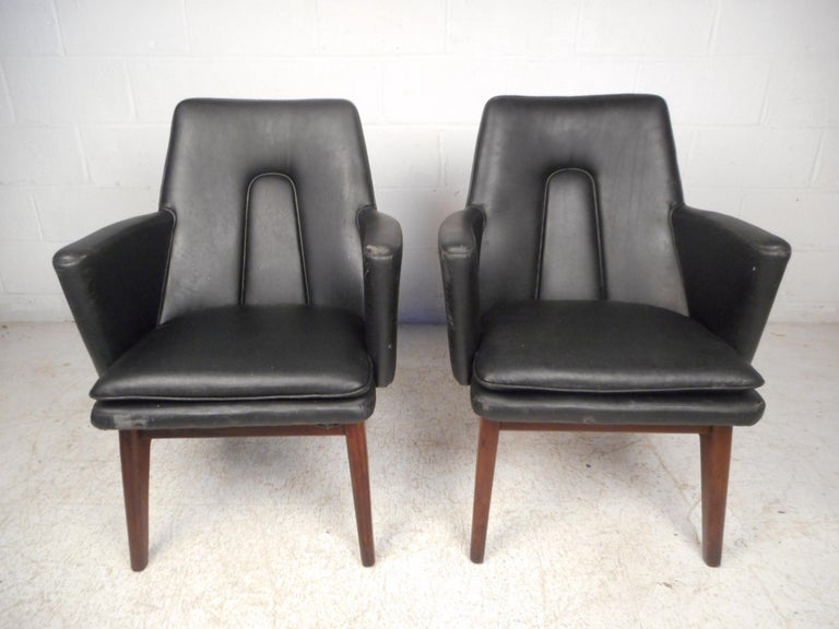 Stylish pair of Danish modern armchairs. Sleek angular seats are supported by sculpted wooden legs, giving these chairs an interesting visual profile. Please confirm item location with dealer (NJ or NY).