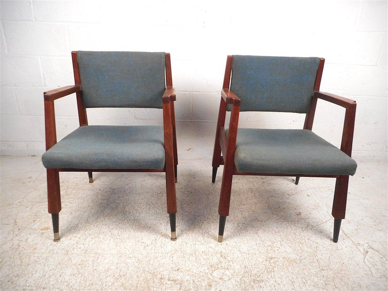 Stylish pair of midcentury armchairs. Sturdy walnut construction with a sleek angular frame, sculpted armrests, and covered in a vintage blue upholstery. This pair is sure to make an impressive addition to any modern interior's seating arrangement.