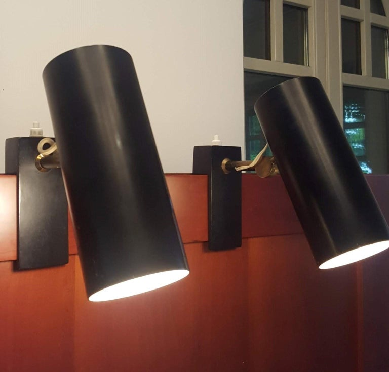 Pair of black lacquered lamps marked Stilnovo on the brass Junction; the Fixing system allows remove or fix them easily thanks to the 'U' connection.  The black and white reflecors can be rotated.  Marked Stilnovo.