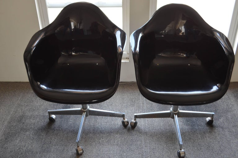 Pair of glossy-black midcentury fiberglass shell chairs. Great condition. Use inside or on porch. Measures: Seat height is 17 inches.