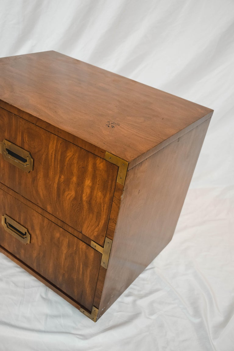 A pair of Campaign style end tables by Dixie Furniture, mid-20th century. This pair of end tables feature a rectangular top and conforming case with two stacked drawers featuring brass hardware. Each piece is hallmarked Dixie Campaigner inside the