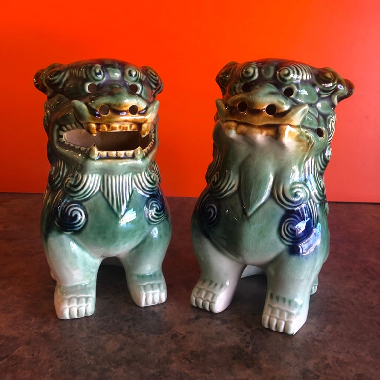 A very nice pair of vintage green, white and blue ceramic foo dogs, circa 1970s. Excellent condition and patina; makes a great pair of book ends or a fun decor item in any room! #1080.