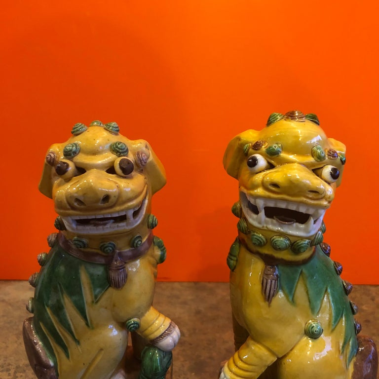 Great pair of midcentury ceramic foo dogs or bookends made in China, circa 1960s. Great detail and a beautiful color combination of yellow, green and brown; the dogs are not a perfect match and may be a married pair, but they go together great and