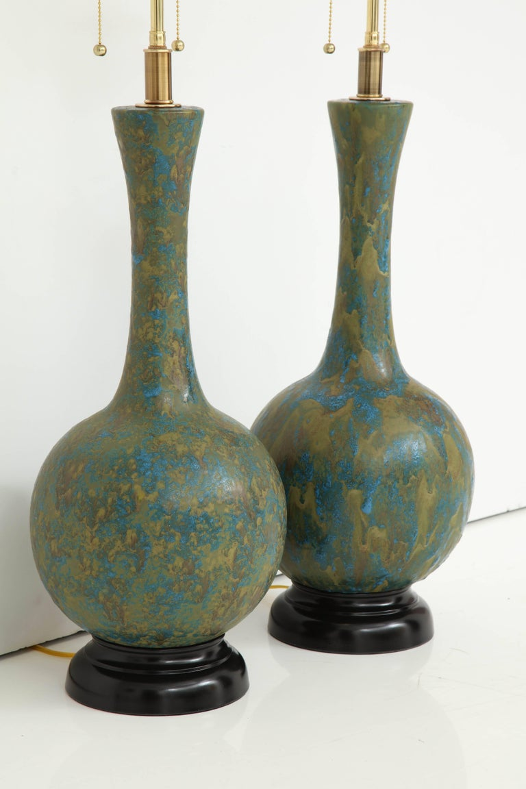 Pair of 1960s Italian Mid Century ceramic lamps with a textured glazed finish. The lamps have been newly rewired for the US with polished Brass double clusters that take standard light bulbs. The overall height of the lamps to the finial is 34.5
