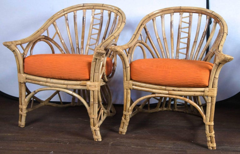 Pair of gracefully curved back rattan arm chairs with corset backs and circle sides. Two orange cushions.