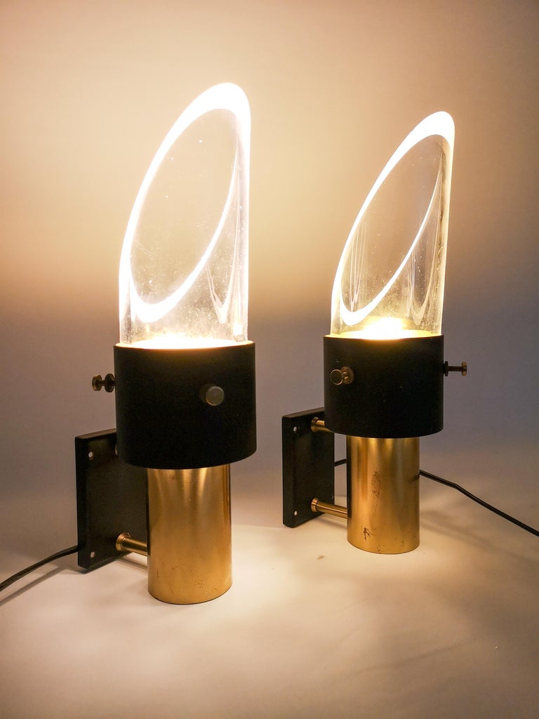 These two midcentury model saga wall lamps was made by Lyfa in Denmark in collaboration with the Swedish company Orrefors. It is made of metal, brass and crystal glass. The wall lamp can be placed upside down and vice versa. The lamp is labeled Lyfa