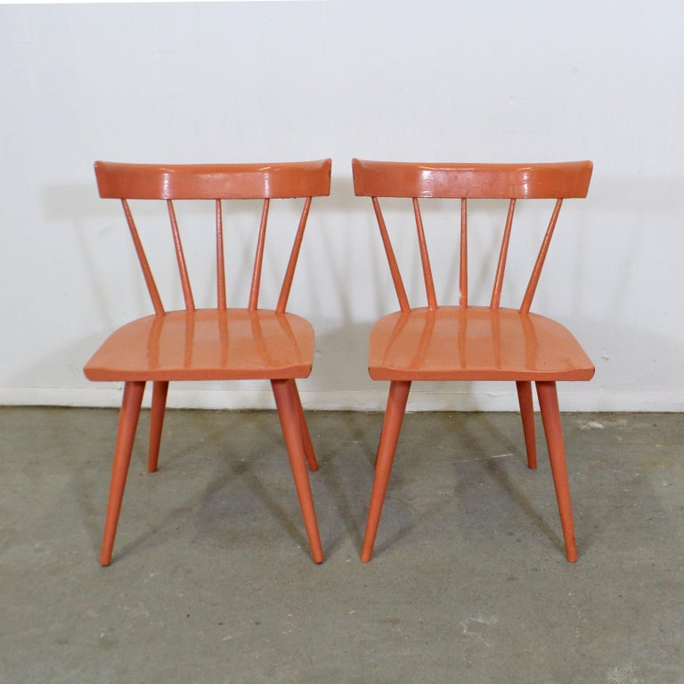 What a find. Offered is a vintage pair of spindle-back side chairs, designed by Paul McCobb for Planner Group. These are solid chair that have been repainted by their previous owner. They are in good, structurally sound condition with some paint