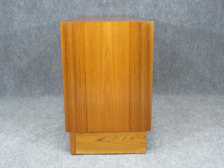 Set of two matching 1960s Mid-Century Modern credenzas with plinth base Danish modern Poul Hundevad for HU teak. Credenzas have 2 doors that glide smoothly and are fronted with sculpted pulls. Well crafted and executed pieces. Marked with HU paper