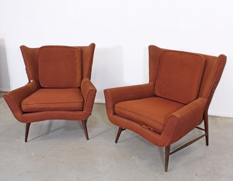 Offered is a pair of vintage mid century wing back lounge chairs. Absolutely incredible lines on these chairs. Featuring a unique shape, with high pencil legs and stretchers, these chairs perfect for any space or design project. Make them your own!