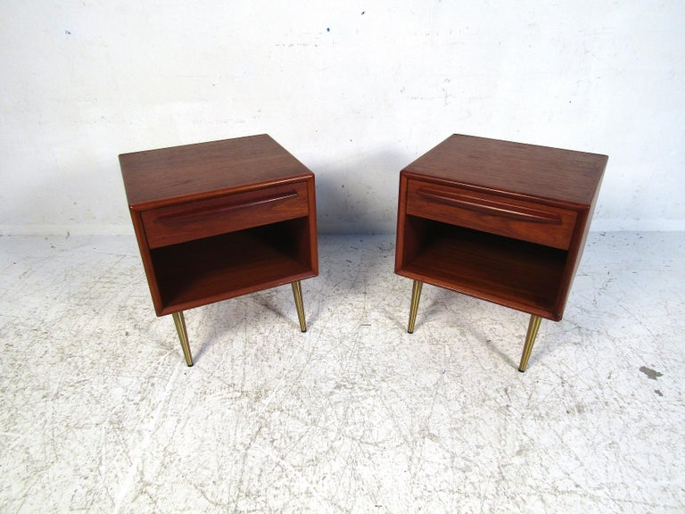 This elegant pair of Danish nightstands feature teak wood and brass legs. Simple in design yet full of style this set will add a degree of sophistication to any bedroom. Please confirm the item location with the dealer. (NJ/NY).