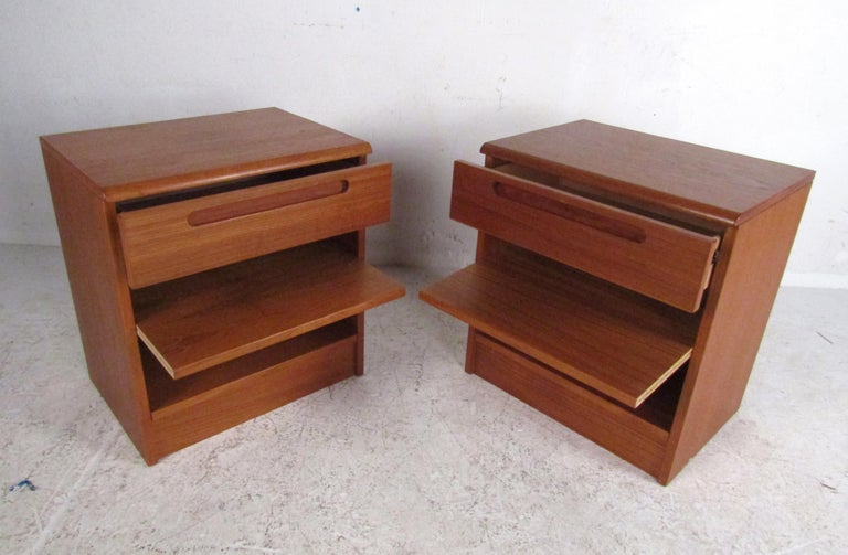 This stunning pair of vintage modern teak side tables feature a large open compartment with a pull-out shelf and a large single drawer. Well-made design stamped,