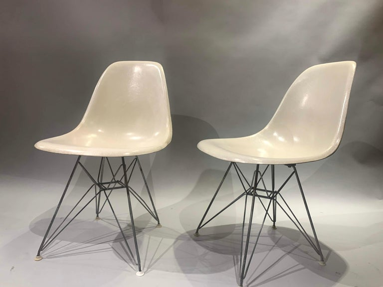A fine pair of midcentury Charles and Ray Eames designed fiberglass side shell chairs for Herman Miller, with ebonized Eiffel Tower form wire bases in fine overall condition, with minimal imperfections and light expected wear. Dimensions: Each