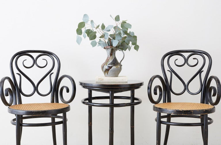 Stunning pair of Mid-Century Modern round bamboo drink tables featuring an ebonized lacquer finish. Elegant and Minimalist style with a round wood top supported by three round bamboo pole legs. The legs are conjoined by a bent bamboo ring stretcher.