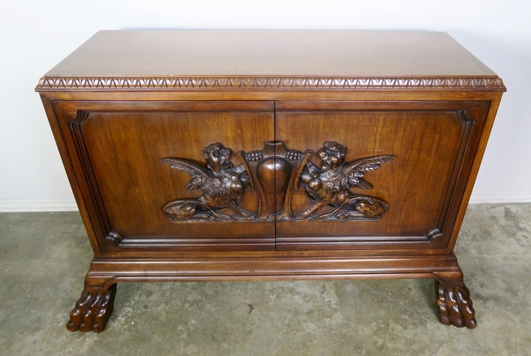 Pair of midcentury English carved mahogany cabinets standing on four lion paw feet. The cabinets are detailed with shields that are flanked with a pair of griffins. There is one shelf available.