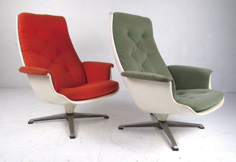 Matching pair of vintage fiberglass shell lounge chairs on swivel bases. Reminiscent of the classic Eames lounge, these stylish chairs are very comfortable and will compliment any home or office environment. Please confirm item location (NY or NJ)